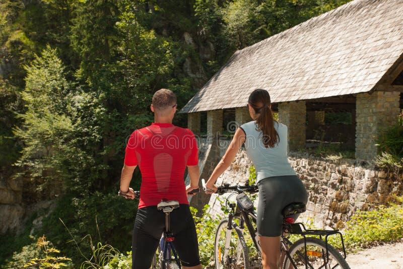 Ciclismo novo ativo dos pares na floresta em um dia de verão quente fotos de stock