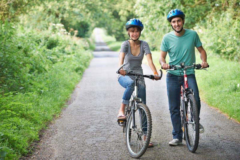 Ciclismo novo dos pares ao longo da estrada secundária fotografia de stock royalty free