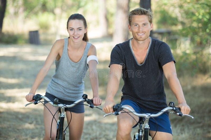 Ciclismo novo dos pares na floresta imagens de stock