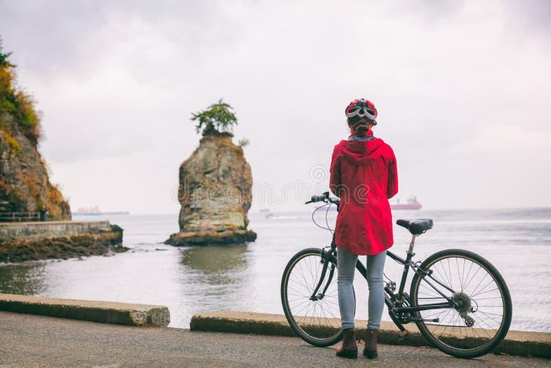 Ciclismo turistico del ciclista della donna della bici della città di Vancouver in Stanley Park, attrazione turistica in Columbia immagine stock