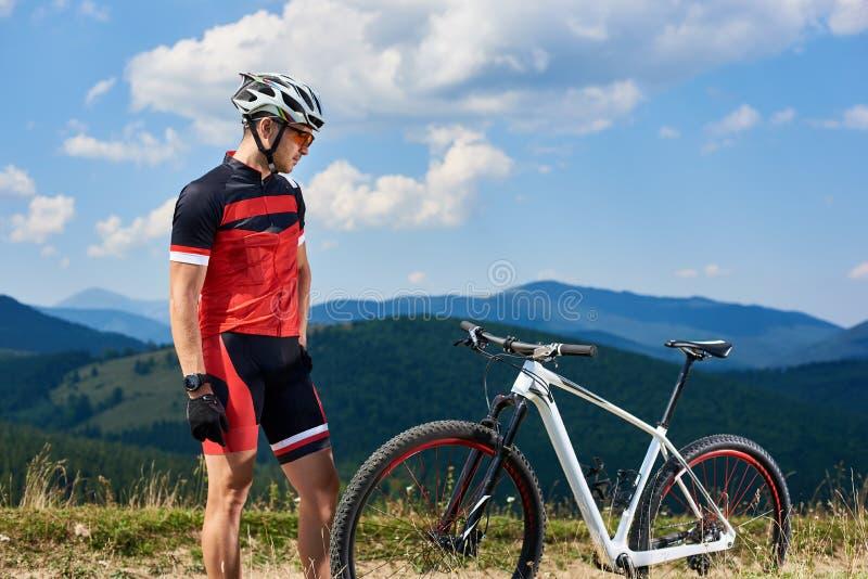 Ciclista atlético do desportista no sportswear profissional e capacete que olha sua bicicleta fotografia de stock