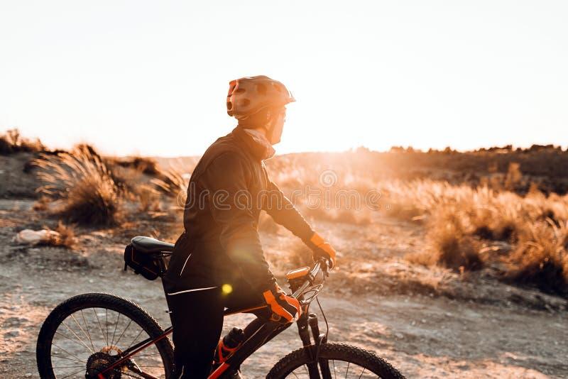 Ciclista che guida la bici giù Rocky Hill al tramonto Concetto estremo di sport fotografie stock libere da diritti