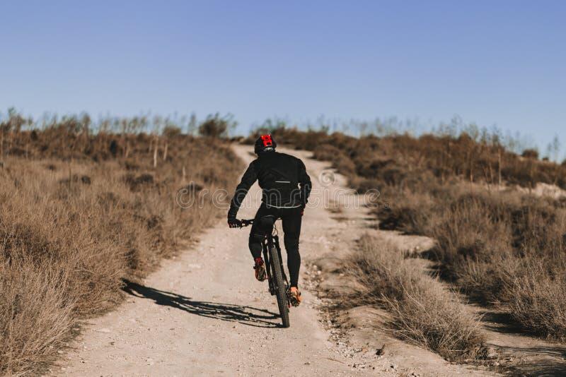 Ciclista che guida la bici gi? Rocky Hill al tramonto Concetto estremo di sport fotografie stock libere da diritti