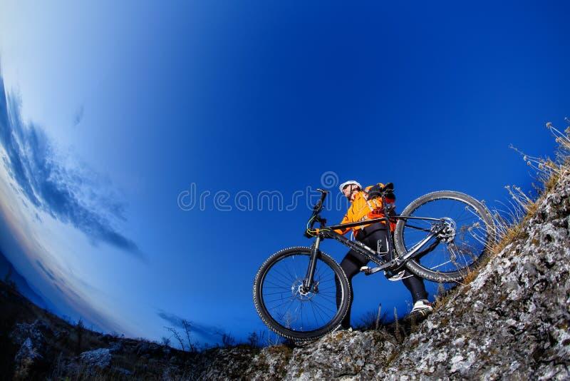 Ciclista che guida la collina della bici giù sulla montagna Rocky Trail al tramonto Sport estremi fotografia stock