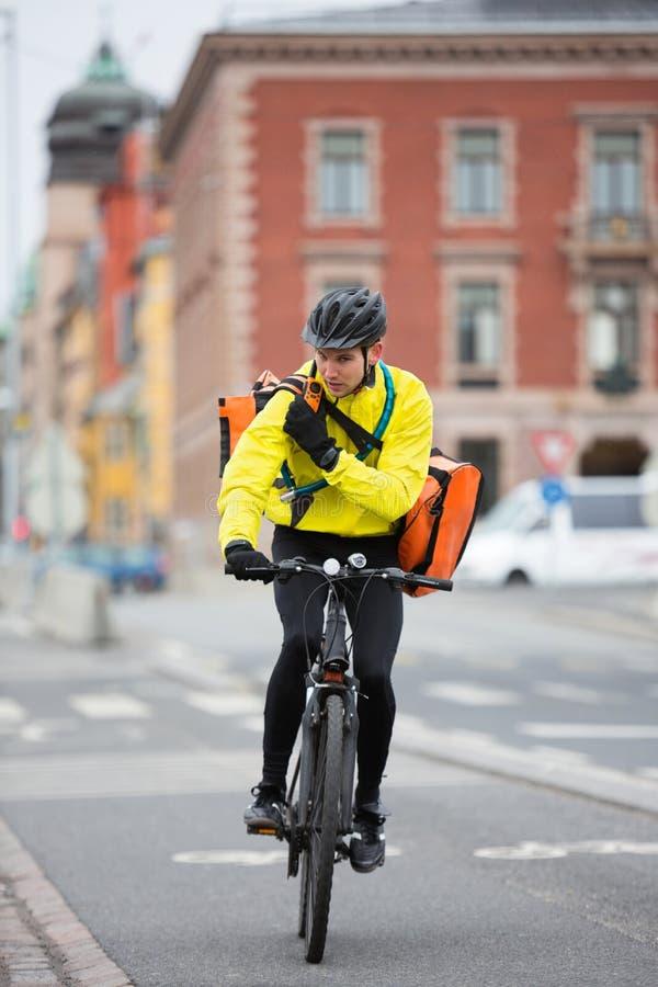 Ciclista con el mensajero Bag Using Walkie-Talkie fotografía de archivo