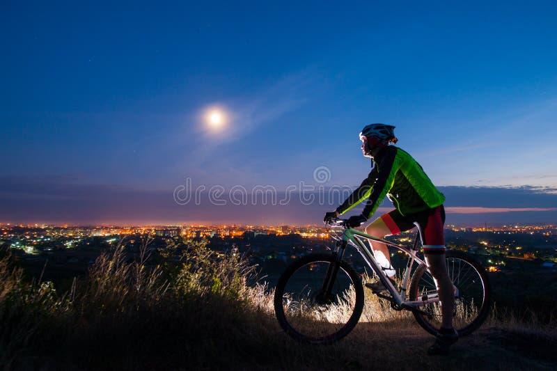 Ciclista con la bici de montaña encima de la colina foto de archivo libre de regalías