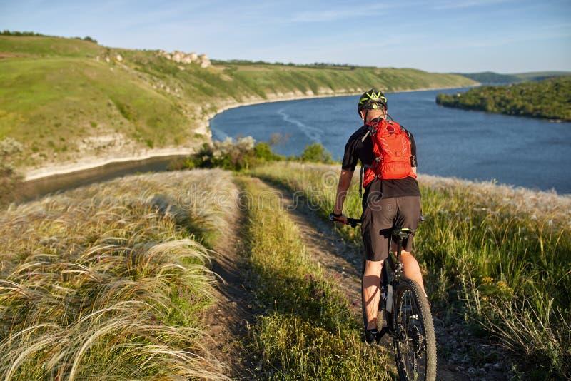 Ciclista con la mochila en su viaje de la bici de montaña en orilla del agua El viajero tiene adventur en prado en la orilla imagen de archivo libre de regalías
