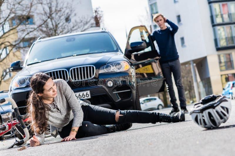 Ciclista con lesiones serias después del accidente de tráfico con un coche imágenes de archivo libres de regalías