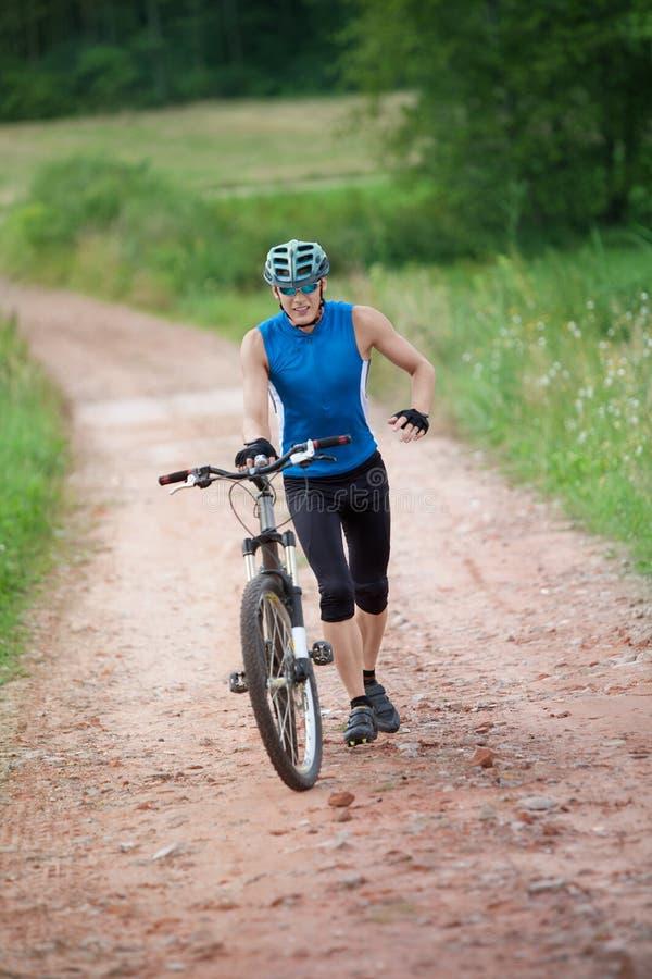 Ciclista corrente che spinge la sua bicicletta fotografie stock libere da diritti