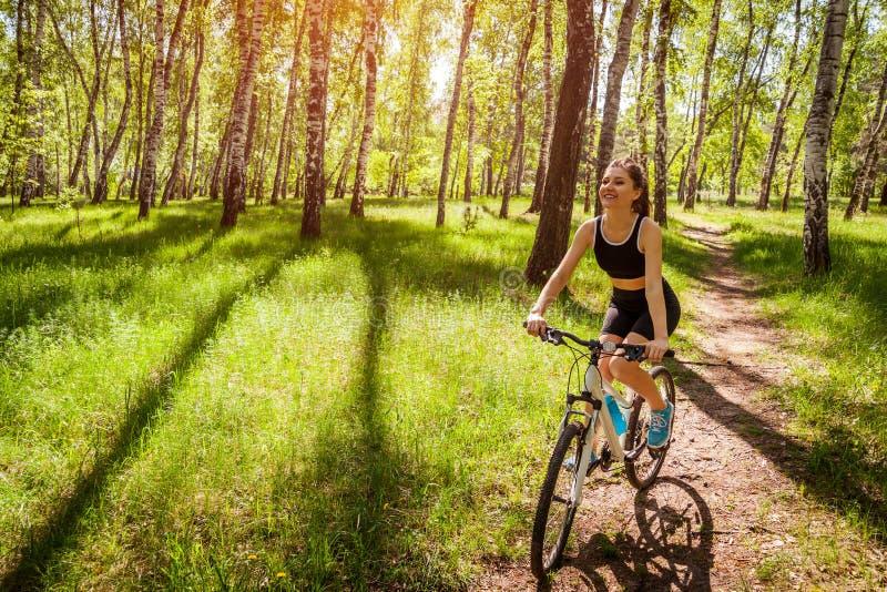 Ciclista da jovem mulher que monta uma bicicleta da montanha na floresta da mola fotos de stock