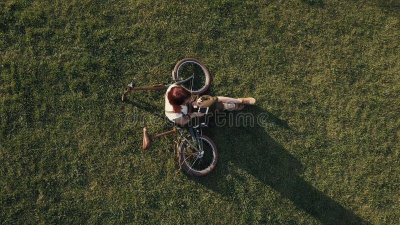 Ciclista da mulher da opinião do zangão que encontra-se na grama verde e que usa o telefone celular foto de stock