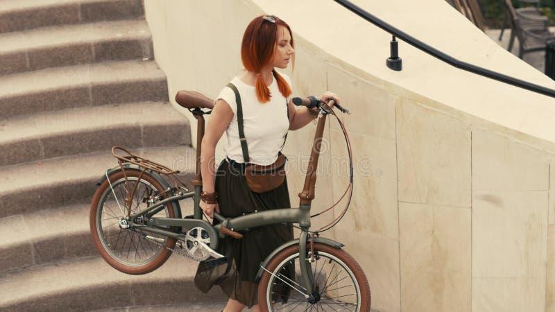 Ciclista da mulher que anda abaixo das escadas e que guarda a bicicleta nos braços Cidade da bicicleta da mulher imagem de stock royalty free