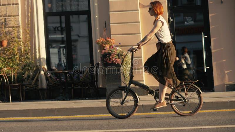 Ciclista da mulher que anda ao lado da bicicleta da equitação na estrada de cidade Cidade da bicicleta da mulher fotografia de stock royalty free