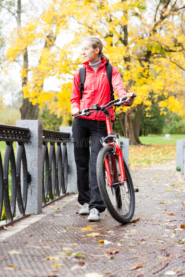 Ciclista de la mujer con la bici en parque del otoño imagenes de archivo