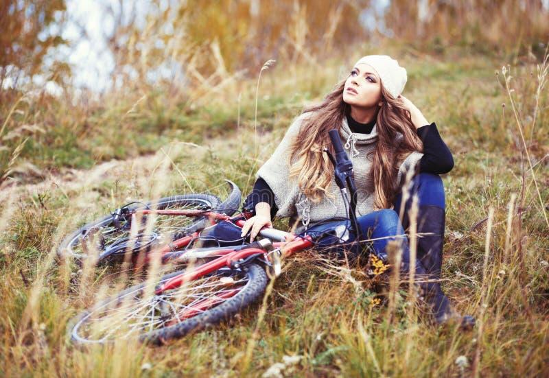 Ciclista de la mujer que se relaja en parque del otoño