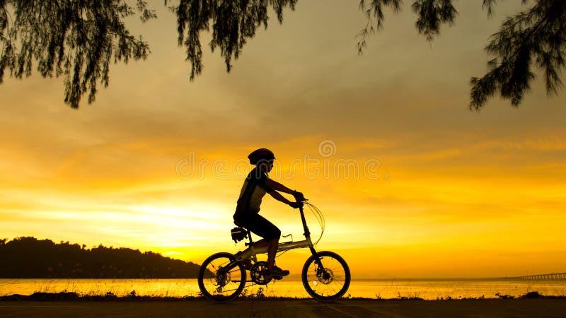 Ciclista de la silueta en la puesta del sol imagen de archivo libre de regalías