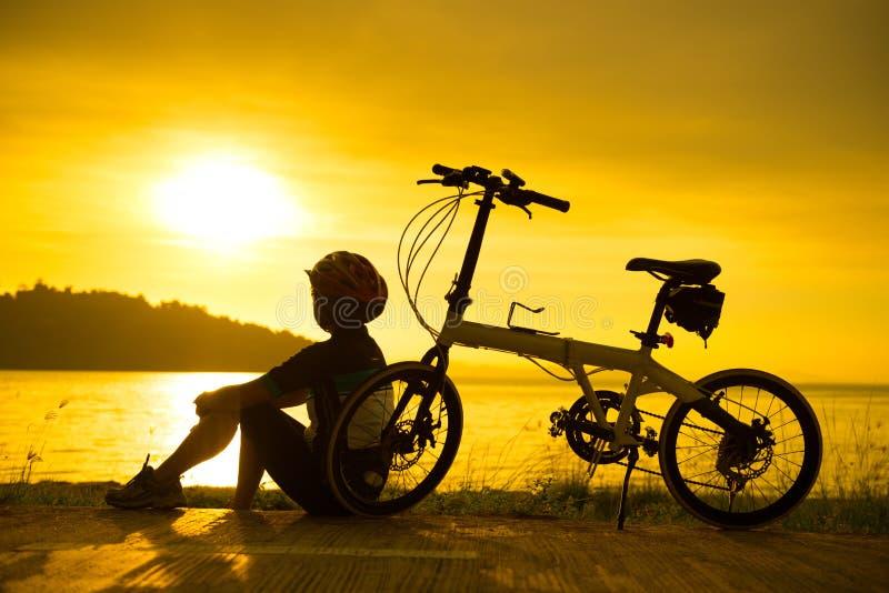 Ciclista de la silueta en la puesta del sol fotos de archivo
