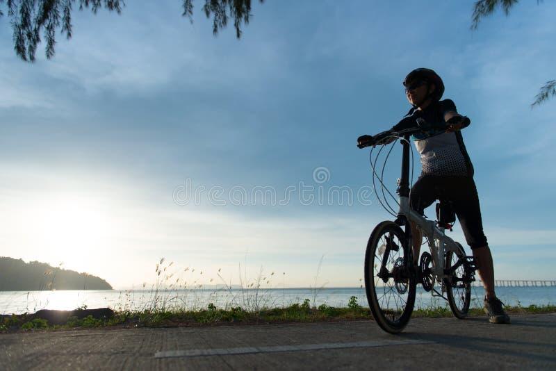 Ciclista de la silueta en la puesta del sol foto de archivo libre de regalías
