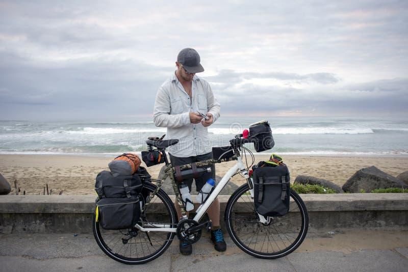 Ciclista de larga distancia con la bicicleta por el océano fotos de archivo