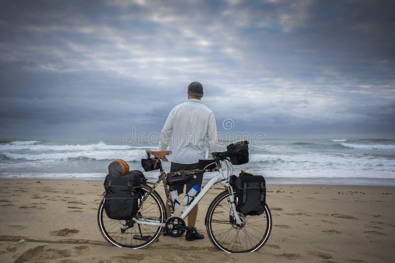 Ciclista de larga distancia en la playa con la bicicleta imagen de archivo libre de regalías