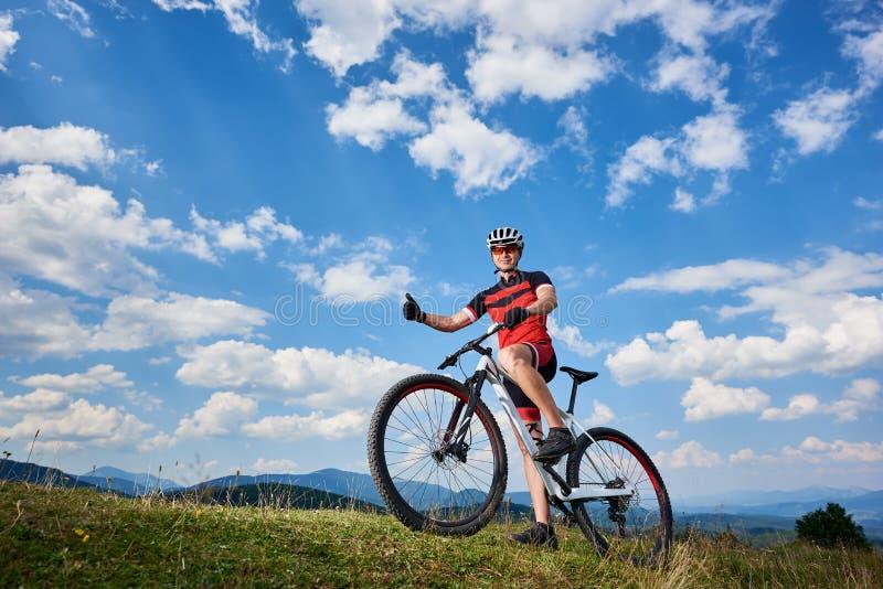 Ciclista de sorriso na posição do sportswear e do capacete com a bicicleta do corta-mato sobre o monte fotografia de stock