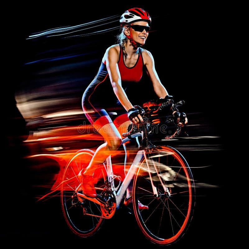 Ciclista del triathlete del triathlon de la mujer que completa un ciclo el fondo negro aislado imagen de archivo