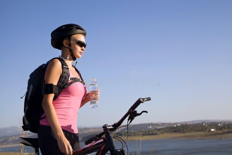 Ciclista della giovane donna con una bottiglia di acqua immagini stock libere da diritti