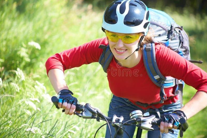 Ciclista della giovane donna nella sosta immagine stock