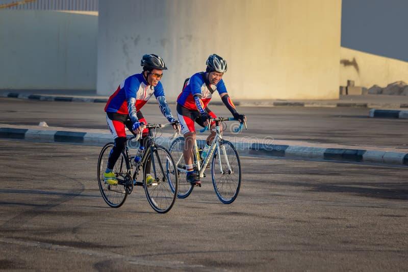 Ciclista dois masculino que dá um ciclo em seu ciclo na estação do inverno Cidade: Dammam, país: Arábia Saudita Mês tomado foto d fotografia de stock royalty free