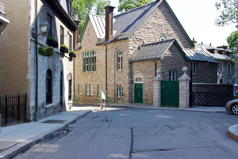 Ciclista, edificio de piedra en la ciudad vieja la ciudad de Quebec, Canadá, verano fotos de archivo libres de regalías