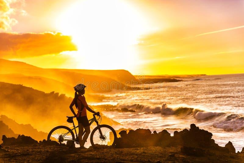 Ciclista el Biking de montaña de MTB que mira la opinión de la puesta del sol imagen de archivo libre de regalías