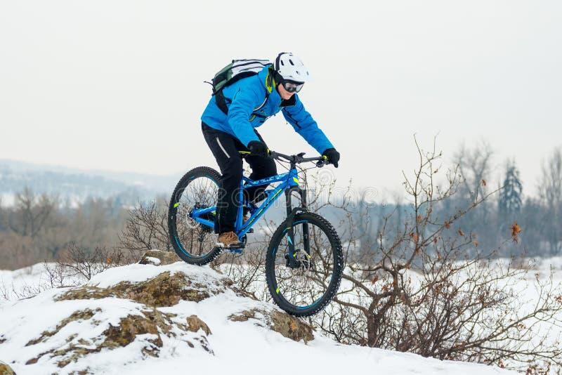 Ciclista en bici de montaña azul del montar a caballo en Rocky Winter Hill Covered con nieve Deporte extremo y concepto Biking de fotografía de archivo