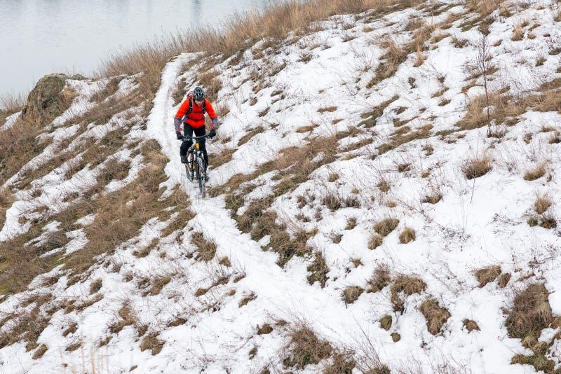 Ciclista en bici de montaña roja del montar a caballo en el rastro Nevado Deporte de invierno extremo y concepto Biking de Enduro fotos de archivo libres de regalías