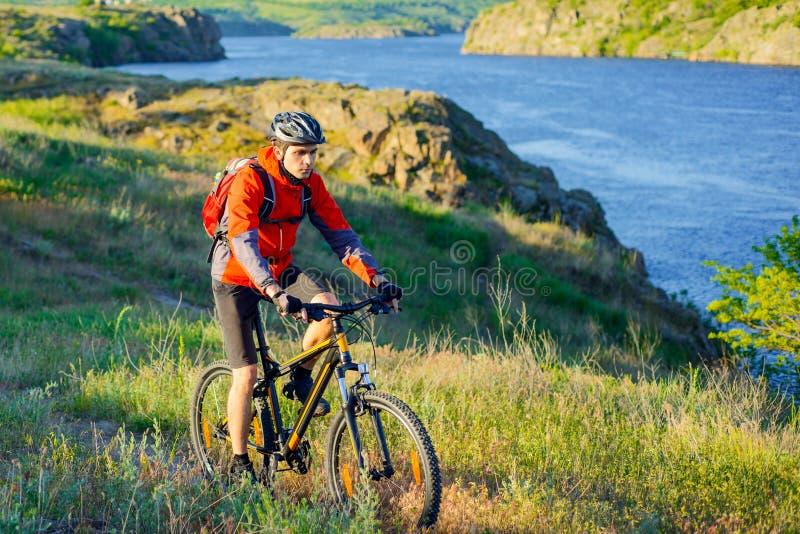Ciclista en bici de montaña roja del montar a caballo de la chaqueta en el rastro hermoso de la primavera sobre el río azul Conce imagen de archivo libre de regalías