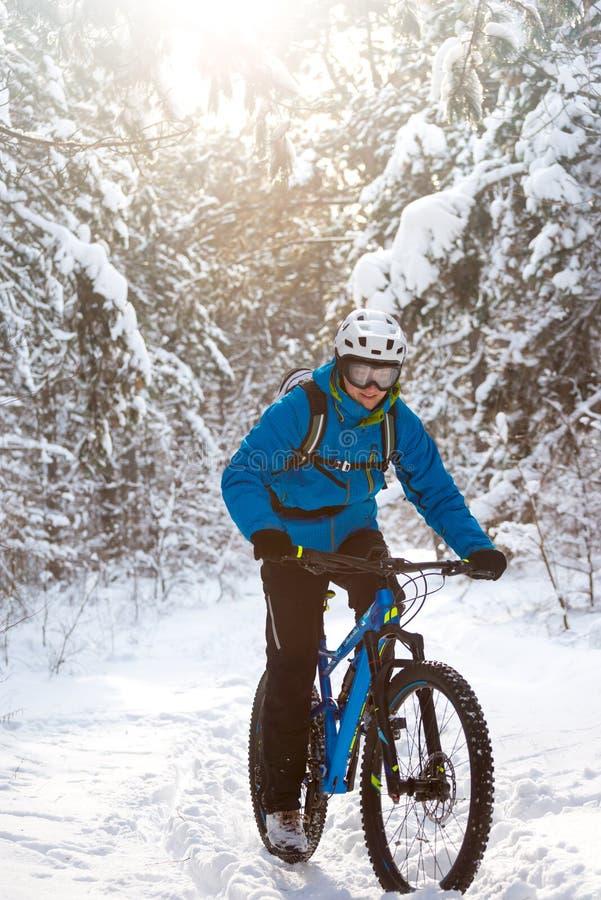 Ciclista en el azul que monta la bici de montaña en el concepto Biking hermoso de Sunny Winter Forest Extreme Sport y de Enduro foto de archivo libre de regalías