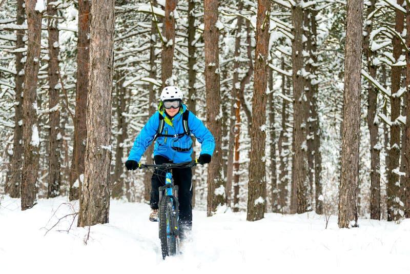 Ciclista en el azul que monta la bici de montaña en el invierno hermoso Forest Extreme Sport y el concepto Biking de Enduro imágenes de archivo libres de regalías