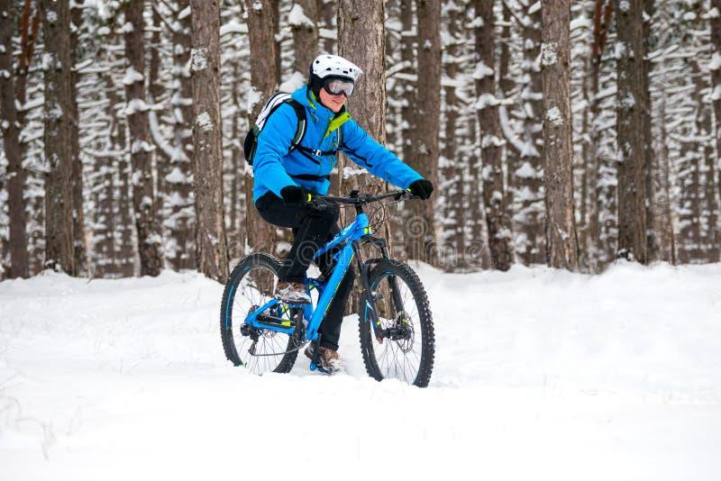 Ciclista en el azul que monta la bici de montaña en el invierno hermoso Forest Extreme Sport y el concepto Biking de Enduro imagen de archivo