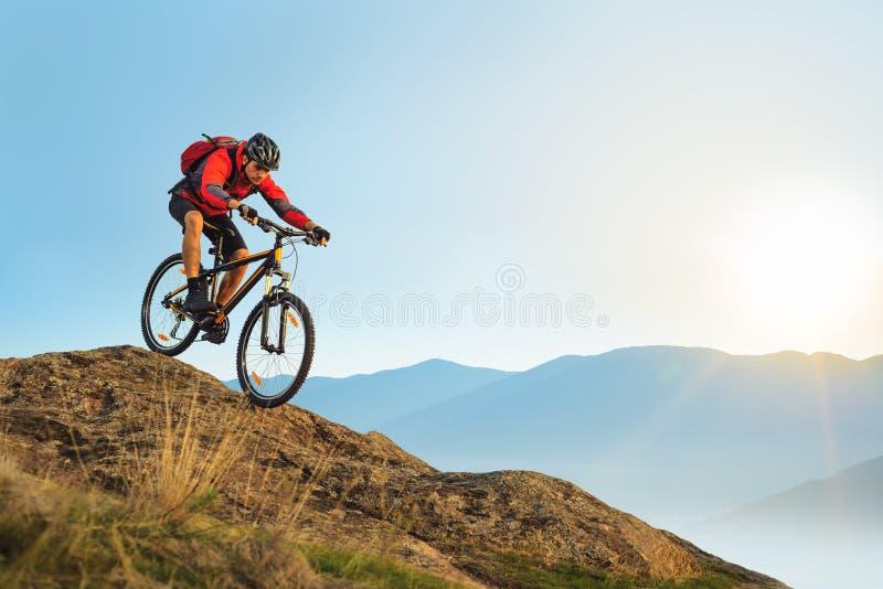 Ciclista en el montar a caballo rojo la bici abajo de la roca en la salida del sol Deporte extremo y concepto Biking de Enduro foto de archivo