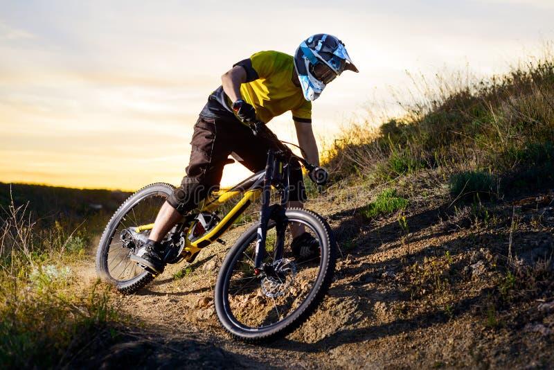 Ciclista en la bici de montaña amarilla de la camiseta y del montar a caballo del casco abajo Rocky Hill Concepto extremo del dep fotos de archivo