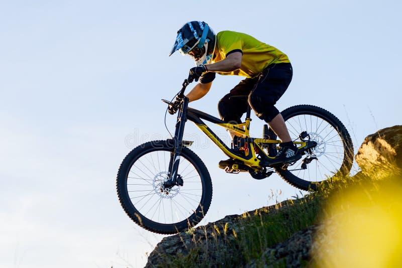 Ciclista en la bici de montaña amarilla de la camiseta y del montar a caballo del casco abajo Rocky Hill Concepto extremo del dep fotos de archivo libres de regalías