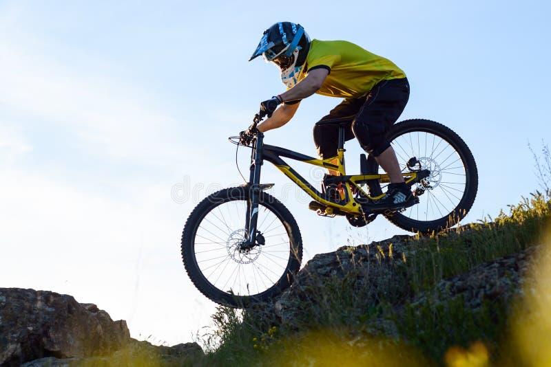 Ciclista en la bici de montaña amarilla de la camiseta y del montar a caballo del casco abajo Rocky Hill Concepto extremo del dep fotografía de archivo