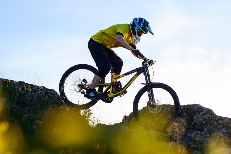 Ciclista en la bici de montaña amarilla de la camiseta y del montar a caballo del casco abajo Rocky Hill Concepto extremo del dep foto de archivo libre de regalías