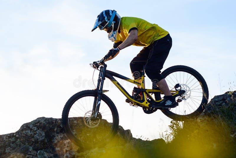 Ciclista en la bici de montaña amarilla de la camiseta y del montar a caballo del casco abajo Rocky Hill Concepto extremo del dep imagen de archivo