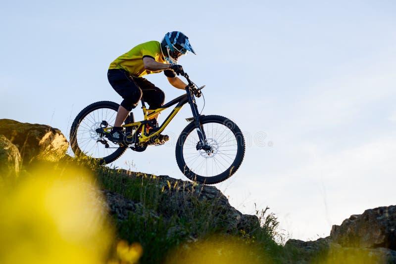 Ciclista en la bici de montaña amarilla de la camiseta y del montar a caballo del casco abajo Rocky Hill Concepto extremo del dep imagenes de archivo