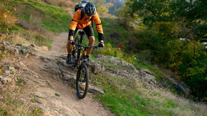 Ciclista en la naranja que monta la bici de montaña en Autumn Rocky Trail Deporte extremo y concepto Biking de Enduro imagenes de archivo