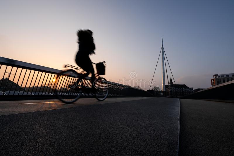 Ciclista en un puente de la bicicleta en Odense, Dinamarca imagen de archivo libre de regalías