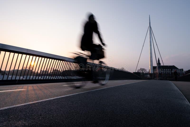 Ciclista en un puente de la bicicleta en Odense, Dinamarca imagenes de archivo