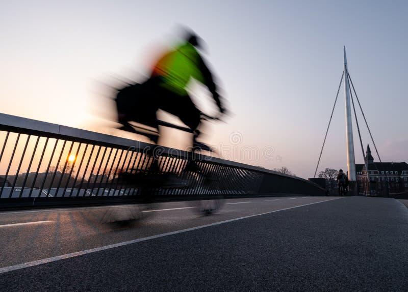 Ciclista en un puente de la bicicleta en Odense, Dinamarca imagen de archivo