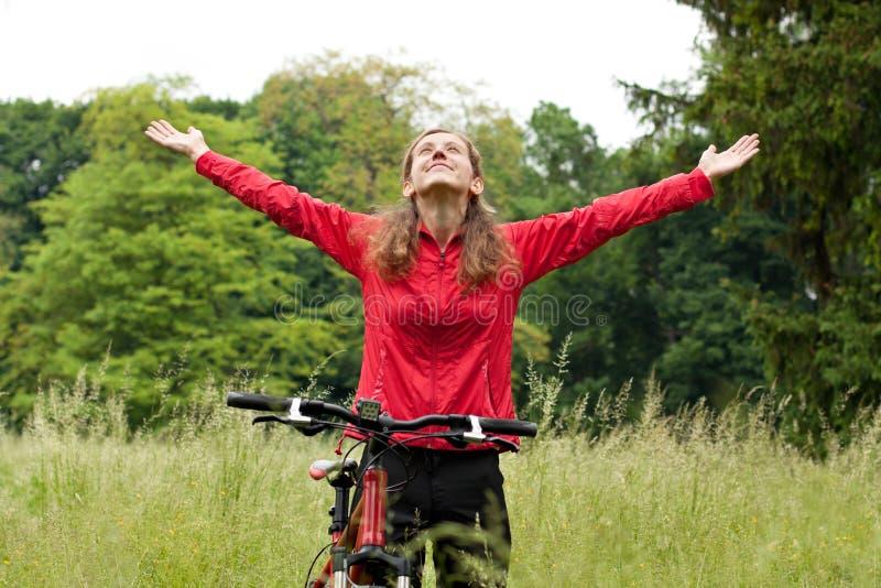Ciclista Excited da mulher com as mãos outstretched fotos de stock royalty free
