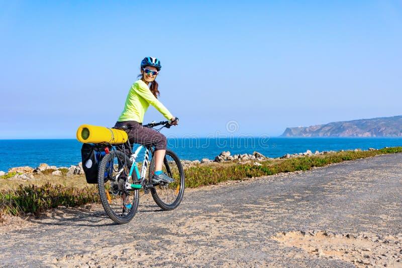 Ciclista fêmea atrativo adulto que monta seu Mountain bike pela costa do oceano e que olha para trás na câmera imagem de stock